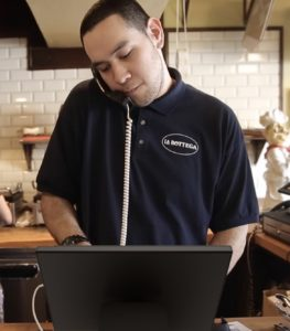 Restaurant employee taking phone order using MobileBytes Caller ID feature.