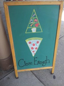Restaurant sign with pizza slice and food pyramid.